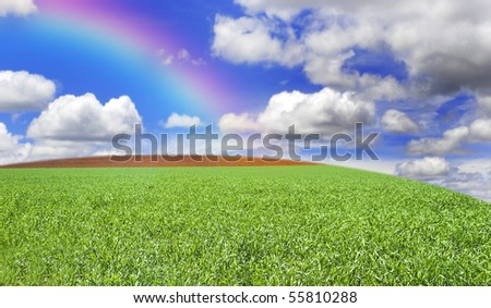 a Grass field hill with beautiful clouds, rainbow and sky