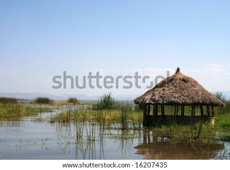 A grass hut in the reeds of a lake in Ethiopia with mountains in the far distance - stock photo
