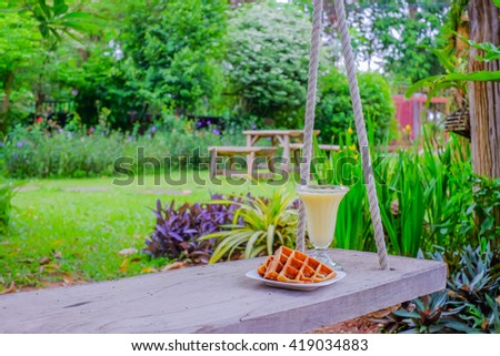 a grass of fruit juices on swing in green garden