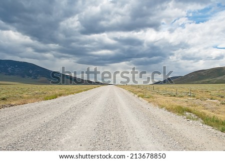 A gravel road runs through a valley in Rocky Mountains of the Western United States under dark storm clouds.