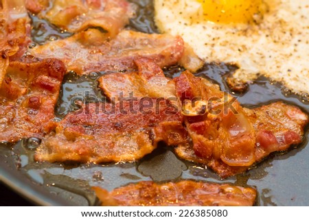 A greasy breakfast of fried bacon and an egg frying in a frying pan. - stock photo