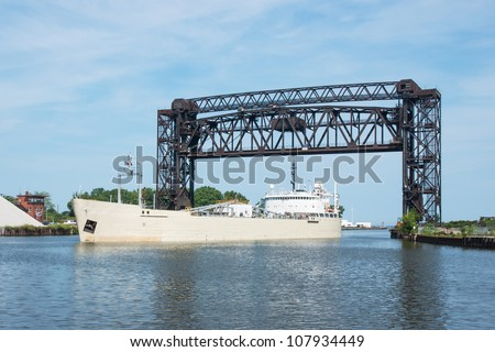 A Great Lakes freighter carrying cement passing under the Norfolk Southern Railroad drawbridge at the mouth of the Cuyahoga River in Cleveland, Ohio