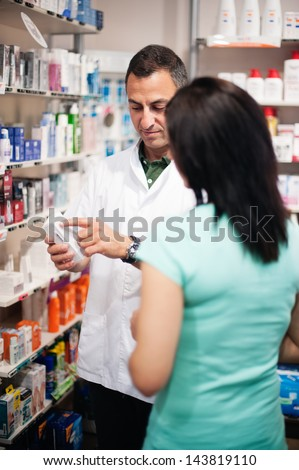 A great professional. The pharmacist resolves all doubts of his client. Photos taken on a real pharmacy. He wears a white coat as uniform - stock photo