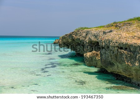 A great side view of a stone cliff hanging over clear warm turquoise tranquil ocean water on a sunny bright day - stock photo
