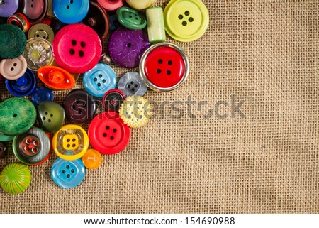 A great variety of colorful vintage buttons against a fabric background. Plenty of copy space. - stock photo