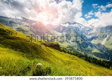 A great view of the green hills glowing by sunlight. Dramatic and picturesque morning scene. Location famous resort Grossglockner High Alpine Road, Austria. Europe. Artistic picture. Beauty world.  - stock photo