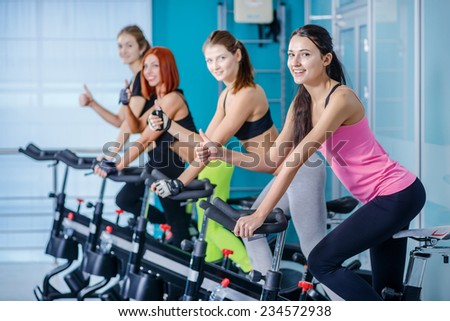 A great workout. Sport girl pedaling on the simulator while four friends athletes pedaling on a stationary bike at the gym show thumbs up. - stock photo
