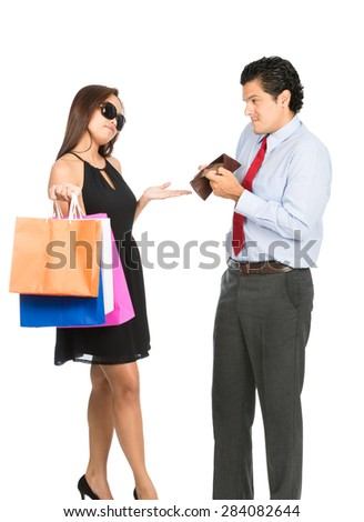 A greedy shopaholic gold digger superficial wife shrugging and demanding cash from her poor husband showing his empty wallet with no money.  - stock photo