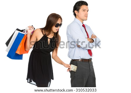 A greedy woman shopaholic with department store shopping bags secretly removing money unnoticed from her pushover husband pants pocket while standing and looking away. H