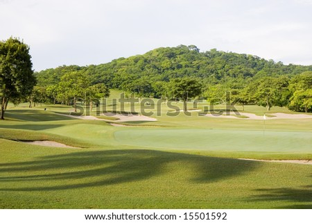 A green and fairway on a golf course in a tropical setting