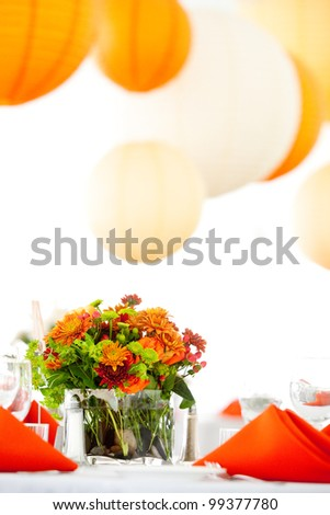 a green and orange wedding centerpiece on a table - stock photo
