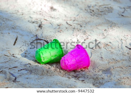 A green and red bucket lying on the beach sand - stock photo