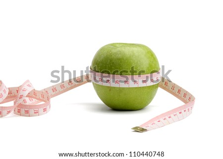 A green apple and a measurement tape , isolated on white background