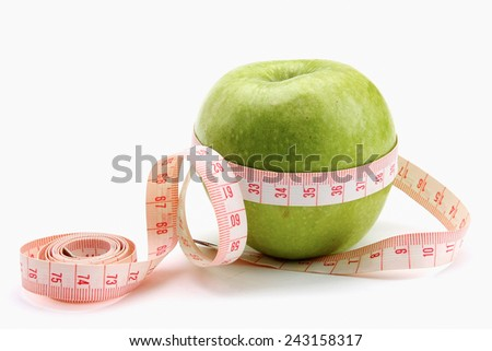 A green apple and a measuring tape