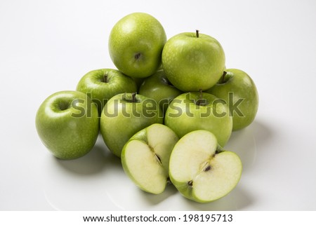 A green apple cut in a half in front of some entire green apples on a white background.