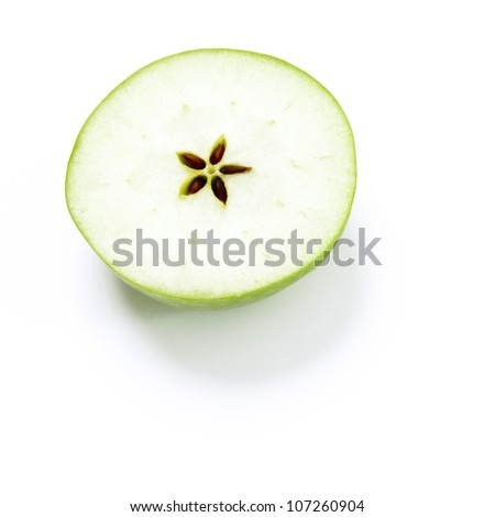 A green apple cut into two halves with a star in the middle. - stock photo