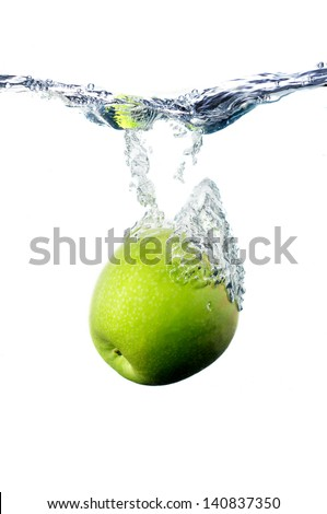 a green apple, falling to the water with the splashing - stock photo