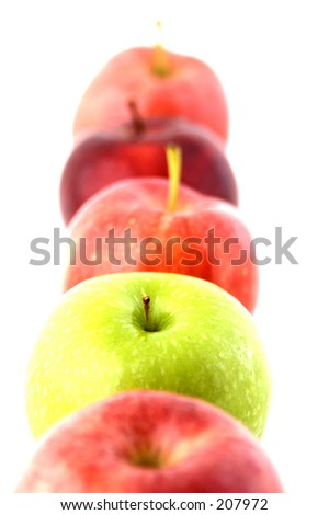 A green apple in a line of red - stock photo