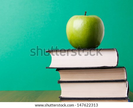 A green apple on a book, closeup