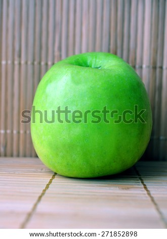 A green apple on the bamboo background