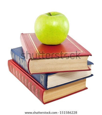 A green apple on top of a stack of old books - stock photo
