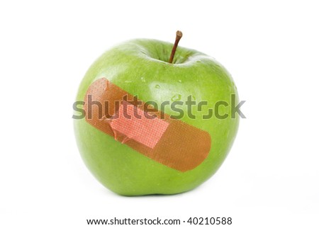 A Green apple with a band-aid on it. - stock photo