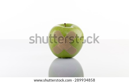 A Green apple with a band-aid on white background - stock photo
