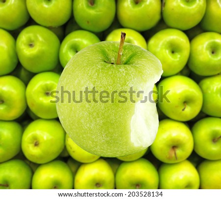 A green apple with a mouth bite against a basket of green apple.