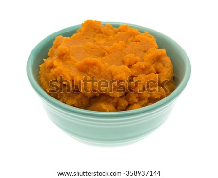 A green bowl filled with pumpkin pie filling isolated on a white background. - stock photo
