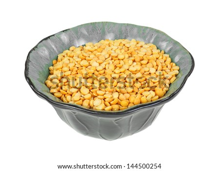 A green bowl of raw yellow split peas. - stock photo