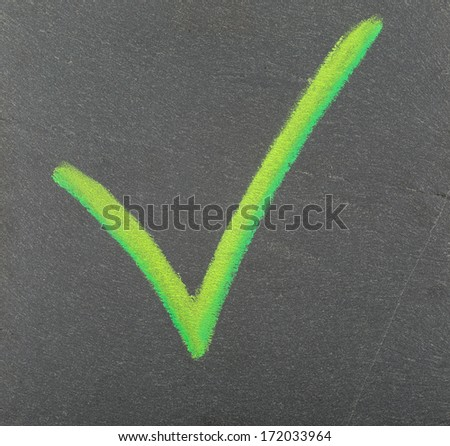 A green check mark, drawn with chalk on a plate of slate.