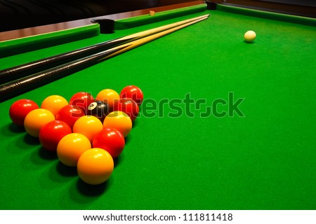 A green cloth billiards or pool table with english league red and yellow balls - stock photo