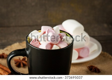 A green cup of hot cocoa with heart shape marshmallows, star anise and cinnamon. Hot drink concept.
