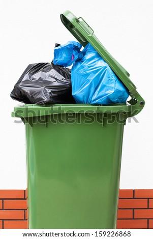 A green dust bin full of rubbish sacks - stock photo