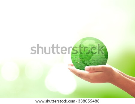 A green earth globe of grass in human hands on blurred beautiful green bokeh background. Environment Mission Investment Insurance Health Care Medical Connection Search Go Green CSR Map concept - stock photo