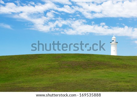 A green field and blue sky with Macquarie Lighthouse on the horizon
