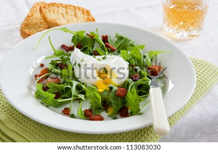 A green French bistro style salad with poached egg and chives on a white plate and table setting - stock photo