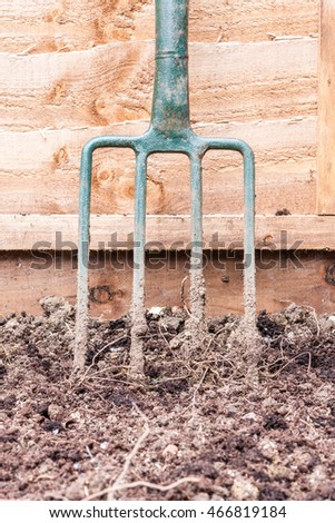 A green garden fork leaning against a wooden fence