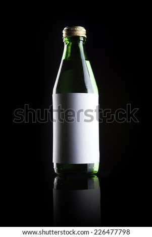 A green glass bottle with blank label and drink reflective bottom isolated black. - stock photo