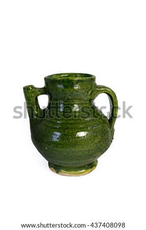A green glazed medieval jug with a spout.