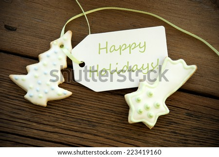A Green Happy Holidays on a Label with Christmas Cookies as Decoration - stock photo