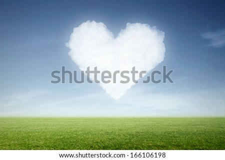 a green meadow with clouds in heart shape in the sky