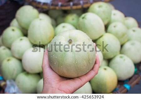 a green melon on hand with background of melons