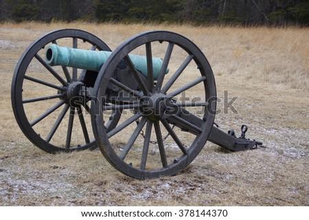 A green, oxidized Civil War cannon in a cold field.               - stock photo