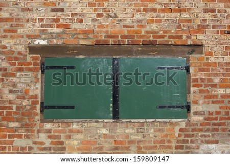 a green painted wooden boarded up window or hatch in a red brick wall background