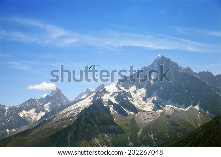 A green paraglider is flying over of french mountain  - stock photo