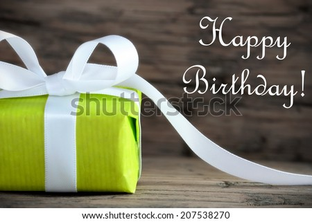 A Green Present with the Words Happy Birthday, on Wooden Background - stock photo