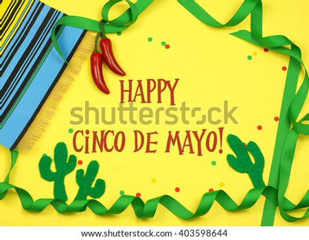 A green ribbon border winds in and out of frame and is decorated with a serape blanket, red chili peppers, felt cutout cactus shapes and confetti on a yellow background with Cinco de Mayo message - stock photo