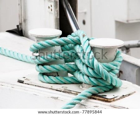 A green rope twisted around a boat - stock photo