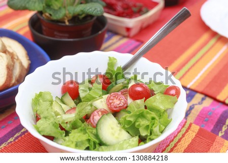 A green salad in a stylish white bowl. With rocket leaves cherry tomatoes spanish onions and capsicum. - stock photo